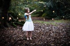 Jong Meisje in Forest Pointing bij Feefonkelingen stock foto's