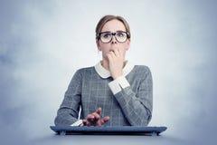Jong meisje in glazen achter het toetsenbord voor de computer in vrees Het concept van de virusaanval royalty-vrije stock foto