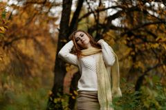Jong meisje in heldere kleren tegen een achtergrond van boomboomstammen in het de herfstbos royalty-vrije stock foto's
