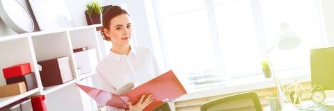 Jong meisje in het bureau dichtbij het rek en rollen door de omslag met de documenten royalty-vrije stock afbeelding