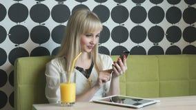 Jong meisje het drinken jus d'orange bij de koffie stock videobeelden