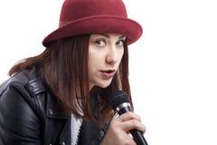 Jong meisje in het jasje van de leerheup en het rode hoed zingen met microp royalty-vrije stock fotografie