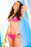 Jong meisje in het roze bikini stellen in summerhouse stock afbeelding