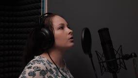 Jong meisje in hoofdtelefoons die lied zingen aan professionele microfoon Registrerende vocale studio stock video