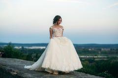 Jong meisje in huwelijkskleding op stadsachtergrond bij zonsondergang De zomer Royalty-vrije Stock Foto's