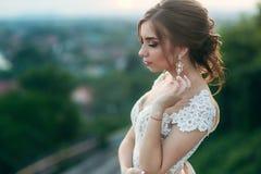 Jong meisje in huwelijkskleding op stadsachtergrond bij zonsondergang De zomer Royalty-vrije Stock Afbeelding