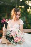 Jong meisje in huwelijkskleding in park het stellen voor fotograaf Zonnig weer, de zomer Stock Afbeelding