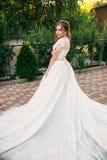 Jong meisje in huwelijkskleding in park het stellen voor fotograaf Zonnig weer, de zomer Stock Foto's