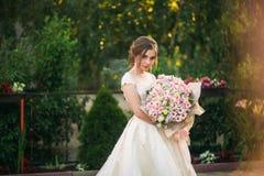 Jong meisje in huwelijkskleding in park het stellen voor fotograaf Zonnig weer, de zomer Stock Afbeeldingen