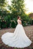 Jong meisje in huwelijkskleding in park het stellen voor fotograaf Zonnig weer, de zomer Royalty-vrije Stock Afbeeldingen