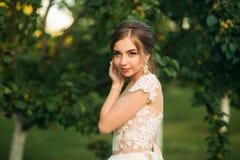Jong meisje in huwelijkskleding in park het stellen voor fotograaf Zonnig weer, de zomer Stock Fotografie