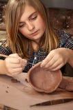 Jong meisje in kleistudio Stock Afbeelding