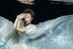 Jong meisje in lange witte kleding onderwater Royalty-vrije Stock Fotografie