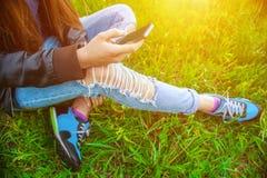 Jong meisje in leerjasje en gescheurde jeans die op het gras in het park zitten en aan vrienden op de telefoon spreken Stock Fotografie