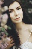 Jong meisje in lilac bloemen Stock Foto