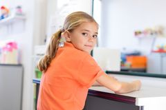 Jong meisje in logopediebureau Het glimlachen gelukkige meisjeszitting voor een spiegel, wachten voor toespraaktherapeut royalty-vrije stock afbeelding