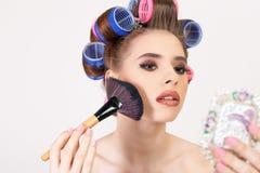 Jong meisje make-up doen en kapsel die krulspelden gebruiken stock fotografie