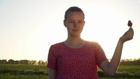 Jong meisje met aardbei bij zonsondergangachtergrond stock footage