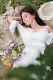 Jong meisje met bloemen in de zomerhoed het stellen op gebied Stock Foto