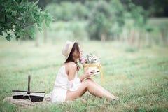 Jong meisje met bloemen in de zomerhoed het stellen op gebied Royalty-vrije Stock Foto's