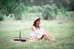 Jong meisje met bloemen in de zomerhoed het stellen op gebied Stock Fotografie