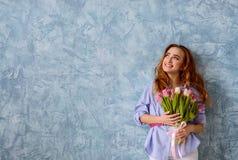 Jong meisje met boeket van bloemen op de blauwe muurachtergrond Stock Foto