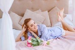 Jong meisje met boeket van bloemen op het bed Royalty-vrije Stock Fotografie