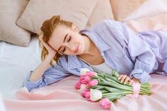 Jong meisje met boeket van bloemen op het bed Royalty-vrije Stock Afbeelding