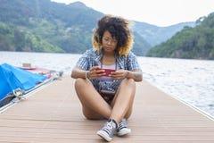 jong meisje met cellphone op de pier royalty-vrije stock fotografie