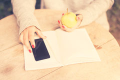 Jong meisje met celtelefoon, agenda en groene appel Stock Fotografie
