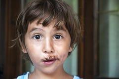 Jong meisje met chocolade op gezicht Stock Foto's