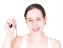 Jong meisje met de sleutel, die over wit wordt geïsoleerd. stock fotografie