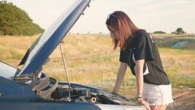 Jong meisje met een gebroken auto met open kap stock video