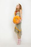 Jong meisje met een gele pompoen Stock Afbeeldingen
