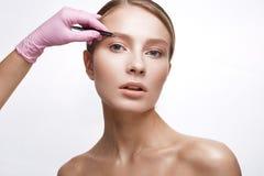 Jong meisje met een gezonde huid en een Naakte make-up Mooi model op kosmetische procedures Plukkende wenkbrauwen en modellering stock afbeeldingen
