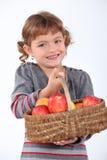 Jong meisje met een mand van appelen Stock Afbeeldingen
