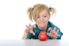 Jong meisje met een rode appel op de lijst.   Royalty-vrije Stock Afbeelding