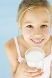 Jong meisje met glas van melk het glimlachen Stock Afbeeldingen