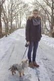 Jong meisje met haar hond op de sneeuw Royalty-vrije Stock Afbeeldingen