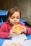 Jong meisje met hamburger Stock Foto