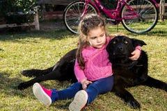 Jong meisje met hond het spelen in tuin stock foto