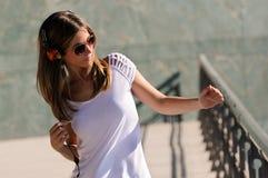 Jong meisje met hoofdtelefoons in de straat Stock Afbeeldingen