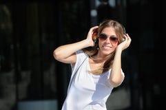 Jong meisje met hoofdtelefoons in de straat Royalty-vrije Stock Foto