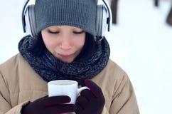 Jong meisje met hoofdtelefoons en koffiekop Stock Afbeelding