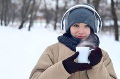 Jong meisje met hoofdtelefoons en koffiekop Stock Fotografie