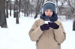 Jong meisje met hoofdtelefoons en koffiekop Stock Foto's