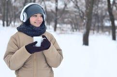 Jong meisje met hoofdtelefoons en koffiekop Stock Afbeeldingen