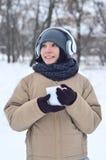 Jong meisje met hoofdtelefoons en koffiekop Royalty-vrije Stock Foto's