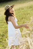 Jong meisje met hooihoed wat betreft tarwe op een gebied Stock Afbeeldingen