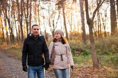 Jong meisje met kerel in de herfstpark royalty-vrije stock afbeelding